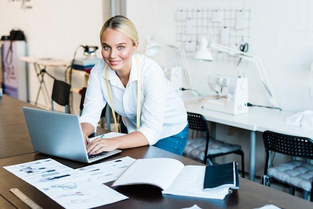 Designer de moda muito jovem e sorridente em roupas casuais, olhando para você enquanto se inclina sobre o laptop e folheia coisas online