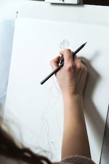 Designer de moda mulher cria um croqui de vestido.