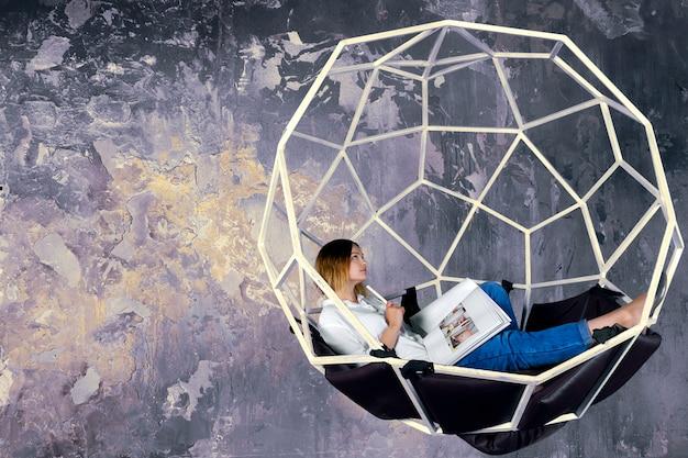 Designer de moda mulher menina feminina com desenhos esboços esboços trabalhando no estúdio de design na esfera do balanço estrutural futurista com almofadas.
