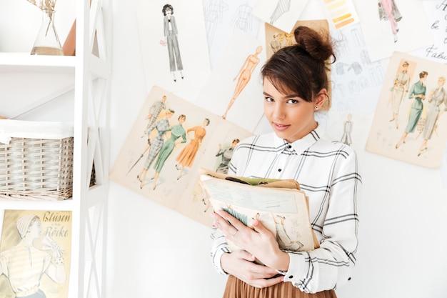 Designer de moda mulher segurando o caderno em pé em seu estúdio