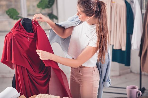 Designer de moda mulher trabalhando em estúdio, sentado na mesa