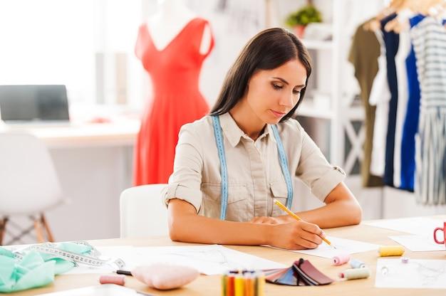 Designer de moda no trabalho. mulher jovem séria desenhando enquanto está sentada em seu local de trabalho na oficina de moda