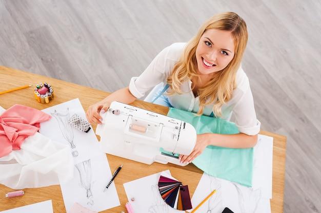 Designer de moda no trabalho. vista superior de uma jovem alegre costurando enquanto está sentada em seu local de trabalho na oficina