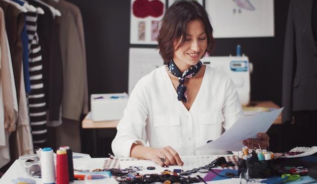 Designer de moda olhando esboços no ateliê de roupas