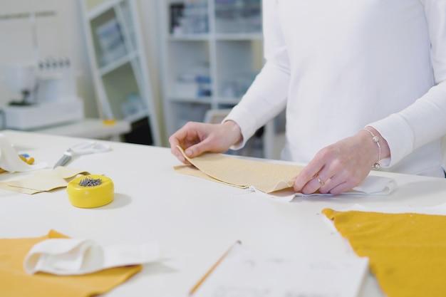 Designer de moda ou tecido de corte sob medida enquanto trabalha com esboço de desenho e material na mesa de trabalho