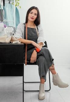 Designer de moda posando em uma cadeira
