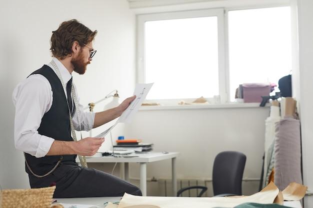 Designer de moda sério examinando os desenhos em suas mãos e trabalhando em uma nova coleção no escritório