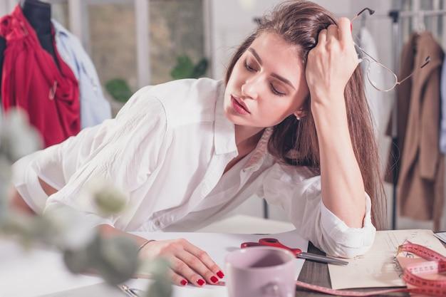 Designer de moda, trabalhando no estúdio, sentado na mesa