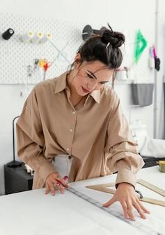 Designer de moda trabalhando sozinha em sua oficina