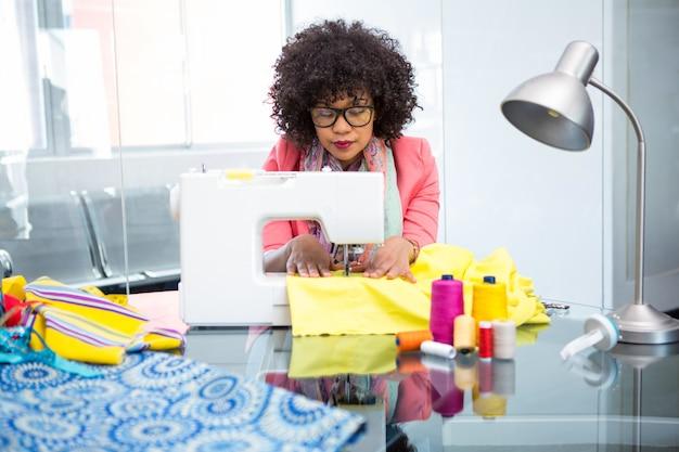 Designer de moda usando a máquina de costura