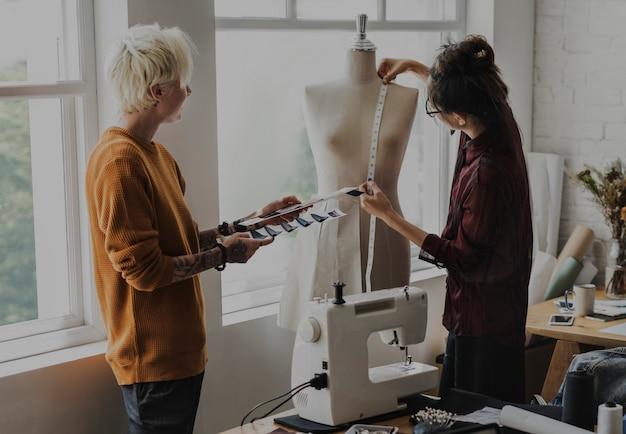 Designer de moda usando uma fita métrica em um manequim