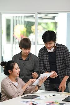 Designer de mulher alegre mostrando o rascunho de um novo projeto para seus colegas enquanto discute e compartilha ideias no escritório.
