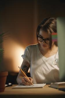 Designer de mulher jovem sério sentado dentro de casa à noite escrevendo notas