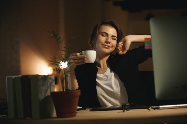 Designer de mulher jovem sorridente, estendendo-se dentro de casa à noite