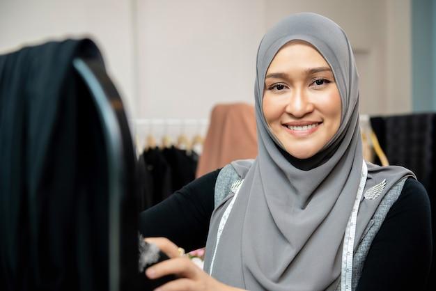 Designer de mulher muçulmana asiática em sua loja de alfaiate