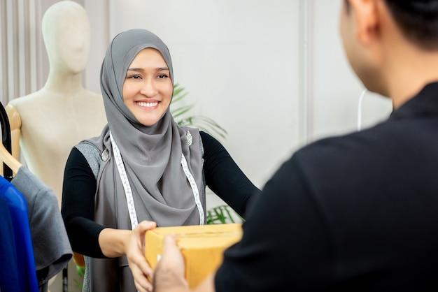 Designer de mulher muçulmana, recebendo a caixa de parcela do entregador