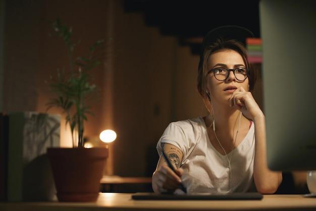 Designer de mulher séria usando computador e tablet gráfico
