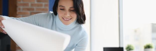 Designer de mulher sorridente em seu escritório. desenvolvimento do conceito de design de apartamentos e moradias
