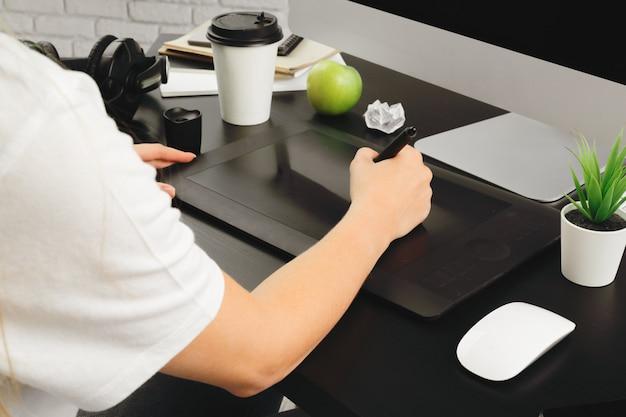 Designer de mulher trabalhando no escritório e usando um tablet gráfico