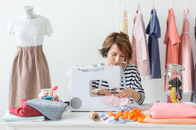Designer de roupas, costureira, conceito de pessoas - costureira trabalhando em seu estúdio
