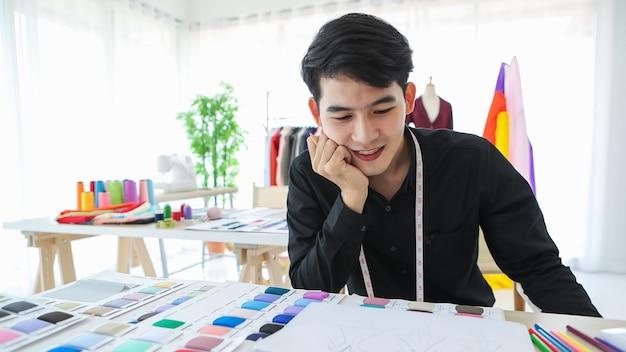 Designer de roupas masculinas étnicas de conteúdo sentado à mesa com tecido e desenhos com uma cara feliz.