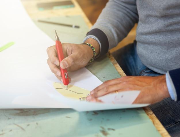 Designer de sapato trabalhando com modelos de papel para corte de couro.
