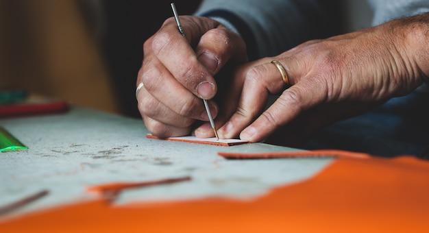 Designer de sapatos trabalhando com couro.