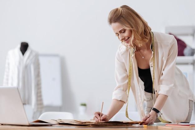 Designer de uma linda mulher sorridente usando uma fita métrica no pescoço e fazendo anotações nos padrões do vestido, tendo um manequim com uma camisa no fundo.