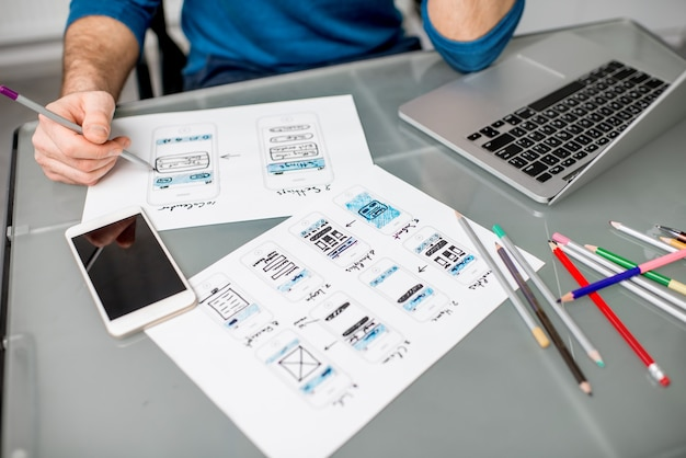 Designer de ux trabalhando na experiência do aplicativo móvel, fazendo esboços de desenhos no escritório. imagem focada sem os desenhos cortados sem rosto