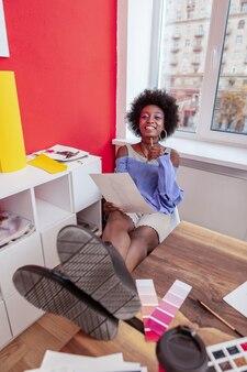 Designer de vigas. designer de moda radiante sentada à mesa com as pernas apoiadas enquanto desenha esboços