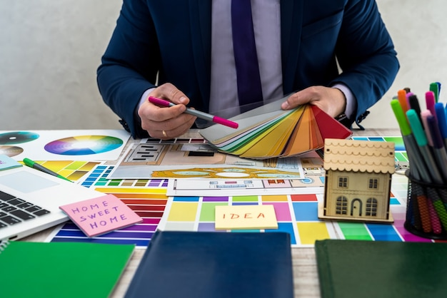 Designer desenvolve um esboço de ilustração interior com esquema de cores do material em uma mesa, local de trabalho de escritório. desktop de um arquiteto e designer de interiores com amostras de equipamentos e materiais