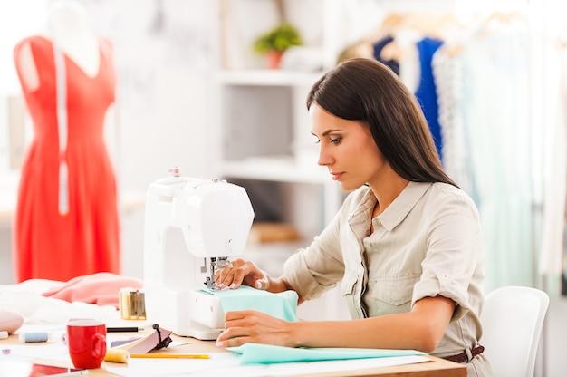 Designer diligente. vista lateral de uma jovem mulher costurando enquanto está sentada em seu local de trabalho na oficina de moda