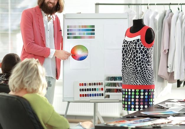 Designer discute com colegas amostras de tecido.