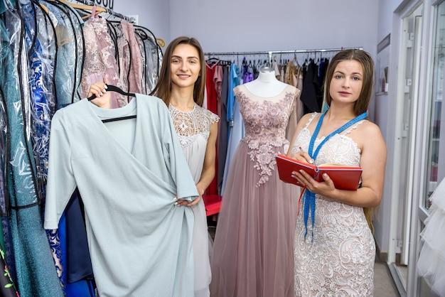 Designer e cliente em loja de roupas com vestido