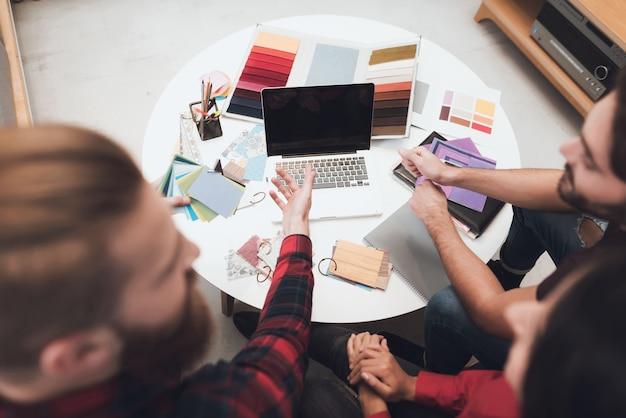 Designer e seus clientes estão examinando padrões de design.