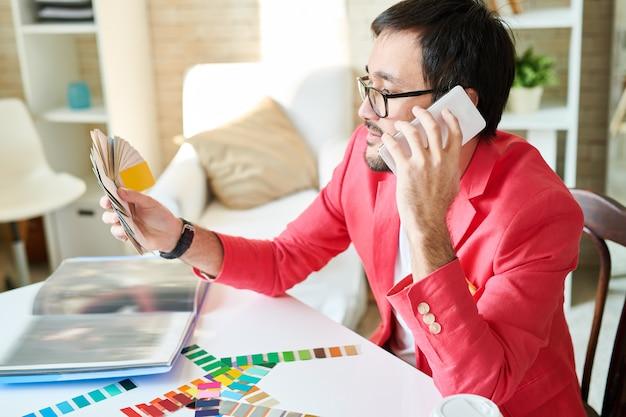 Designer escolhendo cores e falando no telefone