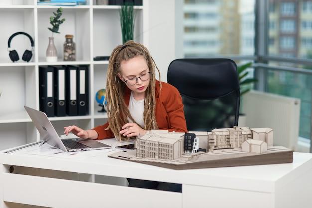 Designer experiente e habilidoso trabalhando com mock up de papelão de área residencial em arquitetura