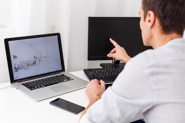 Designer feliz trabalhando em seu laptop no escritório criativo