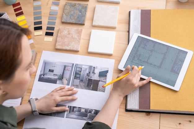 Designer feminina criativa de interiores olhando a planta do apartamento no tablet digital e escolhendo um exemplo de foto por local de trabalho