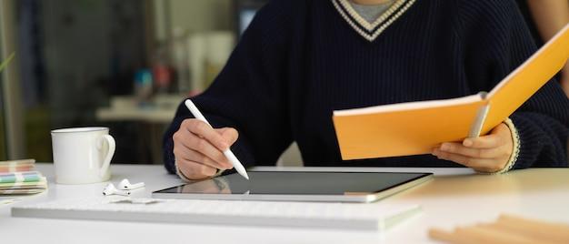 Designer feminina de desenho no tablet digital com caneta e procurando informações no livro de agenda