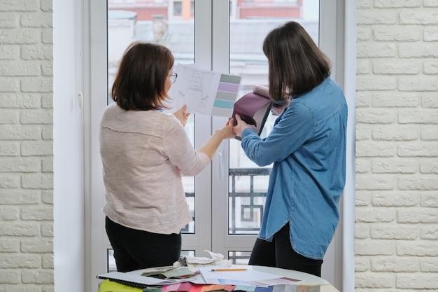 Designer feminina e cliente trabalhando com amostras de tecido.