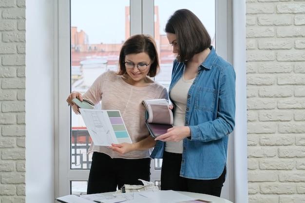 Designer feminina e cliente trabalhando com amostras de tecido