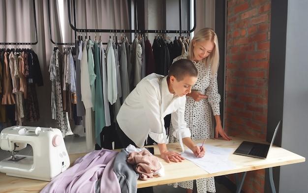 Designer feminina mostra seus esboços de roupas feitas à mão para uma bela cliente. o conceito de design de moda