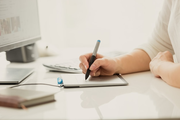 Designer feminina usando tablet gráfico digital enquanto trabalha no computador