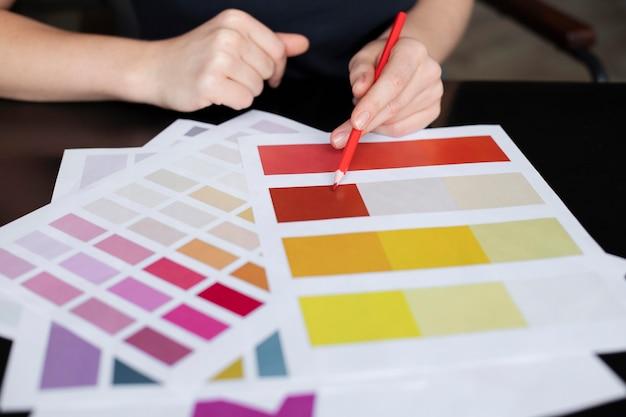Designer feminina verificando as cores da marca em busca de um logotipo