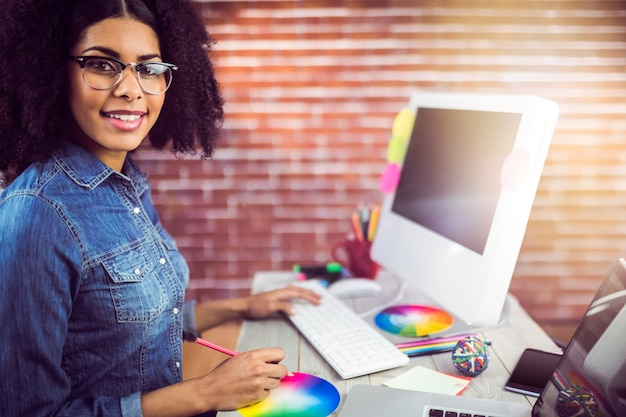 Designer feminino casual sorridente e trabalhando