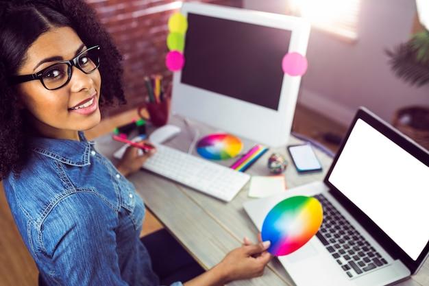 Designer feminino casual sorrindo e segurando gráfico de cores