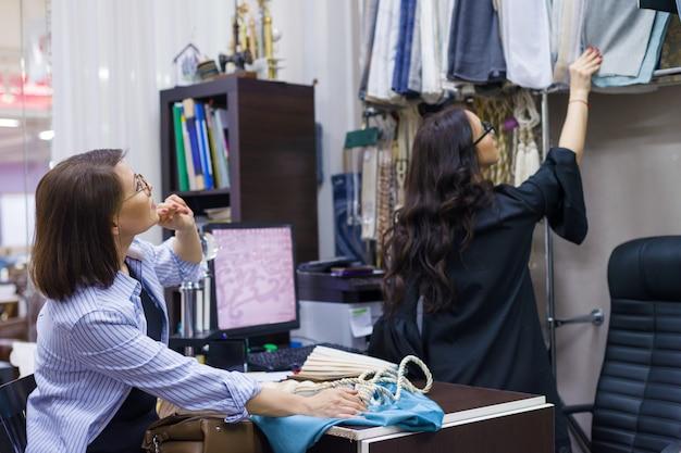 Designer feminino, decorador de interiores, dono de loja mostra o tecido.