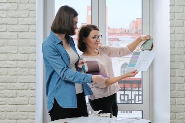 Designer feminino e cliente trabalhando com amostras de tecido