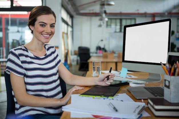 Designer gráfica feminina sorridente, sentada à mesa com o tablet gráfico e a área de trabalho na mesa